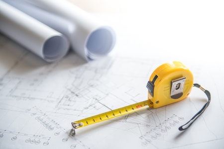 architectural drawing plan of house project, blueprint rolls and yellow tape measure (measuring tape) on work table, building construction industry concepts