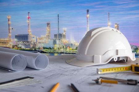 architectural drawing plan of refinery plant with blueprint rolls, protection safety helmet and project tools on work table, building construction industry concepts Stockfoto