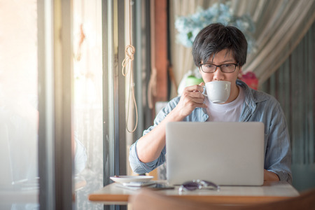 Young Asian happy man using laptop during coffee time in cafe, casual lifestyle in summer holiday or vacation time concepts Stock Photo