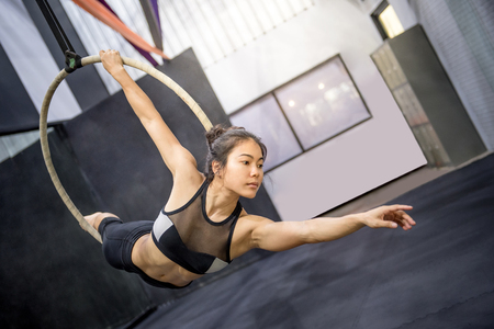 sexy girl dance: young asian acrobatic woman doing her gymnastics performance on aerial hoop or aerial ring