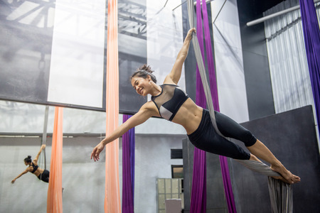 Young Asian woman doing anti-gravity yoga or fly yoga in aerial gym Stock Photo