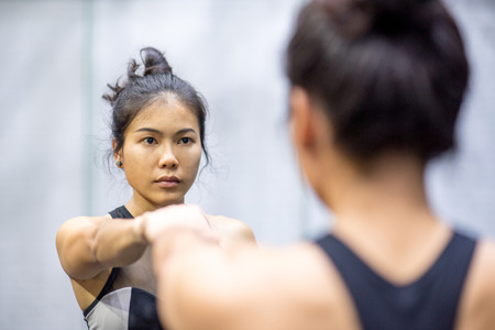 young asian athletic women in sportswear punching and looking herself in the mirror