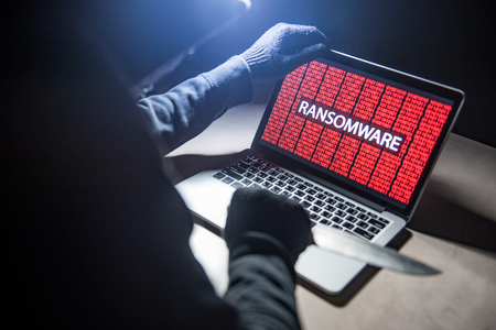 Male hacker threading computer laptop with knife showing on screen with ransomware warning, internet security system concept Stock Photo