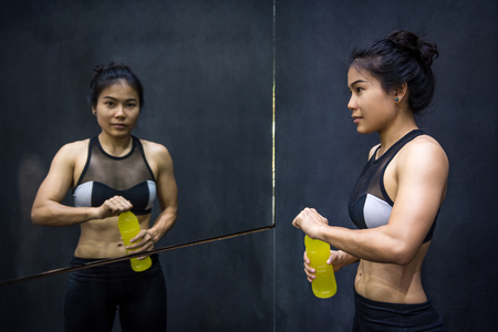 Young Asian athlete woman drinking sport drink or energy drink after exercise in fitness gym, healthy lifestyle concepts Stock Photo