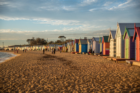 brighton: MELBOURNE, AUSTRALIA - JULY 18, 2016 : Tourists walk pass colorful bathing boxes at Brighton Beach near Melbourne, Australia.