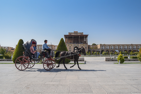 ISFAHAN, IRAN - OCTOBER 22, 2016 : Iranian tourists sit on carriage during visit the Naghsh-e Jahan Square (Imam Sqaure), UNESCO World Heritage Sites in Isfahan (Esfahan), Iran. Editorial