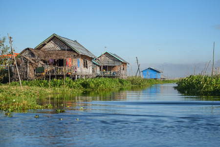 Traditional wood house with gable roof and green floating garden in the village on Inle lake, located in the Nyaungshwe Township of Taunggyi, Shan State, Myanmar Stock Photo