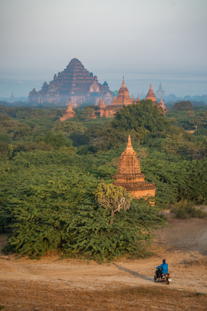 Unidentified man with motorbike among beautiful landscape of ancient pagoda and temple in Bagan archaeological site, famous destination in Mandalay Region, Myanmar (Burma) and Southeast Asia