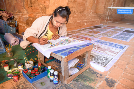 BAGAN, MYANMAR - DECEMBER 22, 2016 : Burmese artist woman draw a beautiful art painting inside the ancient pagoda of Bagan archaeological zone, Mandalay region, Myanmar.