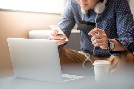 Jeune homme asiatique moitié visage détenant une carte de crédit et à l'aide de smartphone pour faire des achats en ligne dans son espace de travail, concept de style de vie urbain Banque d'images