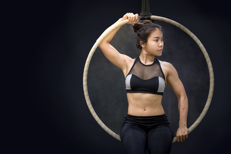 young asian acrobatic woman posturing on aerial hoop or aerial ring, gymnastics exercise on black background Stock Photo