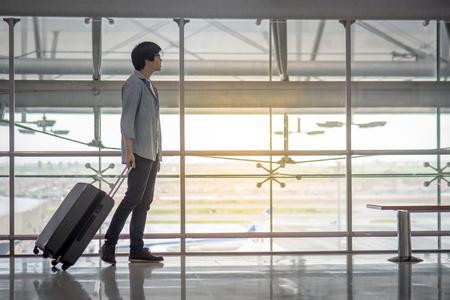 空港スーツケース荷物、旅行生活でターミナルで歩く若いアジア男