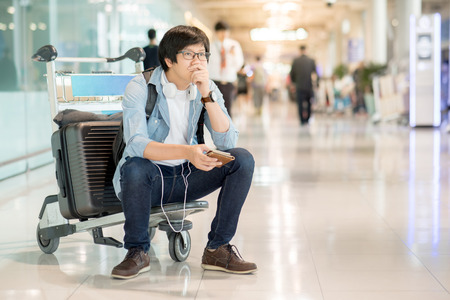 Young Asian man feeling exhausted sitting on airport trolley with his suitcase luggage in the international airport terminal, flight problem and travel insurance concepts