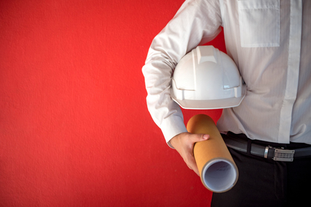 Engineer or Architect holding personal protective equipment safety helmet and architectural drawing in red background. Engineering, Architecture and building construction management concepts Stock Photo