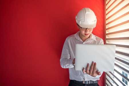 louver: Young Asian Engineer or Architect dressed in white shirt and protective helmet working with laptop computer with red wall in background. Engineering, Architecture and building construction concepts Stock Photo