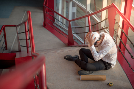 エンジニアまたは建築家疲れて、彼は仕事に頭痛。建物の建設現場で保護具安全ヘルメットを着用しながら彼の側に建築図面の階段の上に座ってく 写真素材