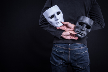 흑백 마스크를 들고 신비 남자입니다. 익명의 사회적 마스킹 개념.