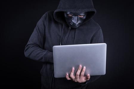 익명 남성 해커 랩톱 컴퓨터를 들고 그의 얼굴을 커버 블랙 마스크를 사용 하여. 인터넷 보안 및 사이버 공격 개념.