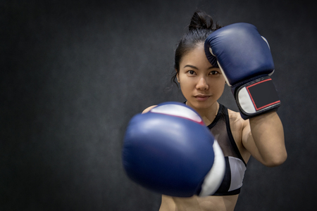 Beautiful young Asian woman posing with blue boxing gloves, black background Stock Photo