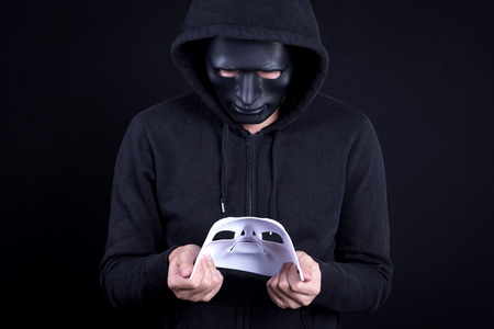 Mystery man wearing black mask holding and looking at white mask. Anonymous social masking or halloween concept. Stock Photo
