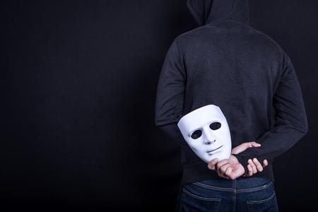 미스테리 남자 다시에서 흰색 마스크를 들고입니다. 익명의 사회적인 마스킹 개념.