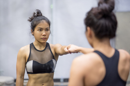 sexy asian woman: young asian athletic women in sportswear punching and looking herself in the mirror