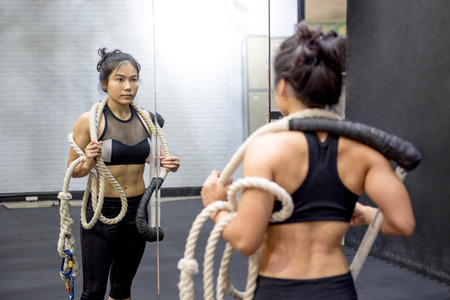 sexy asian woman: Young Asian gymnast woman carrying ropes on shoulders for gymnastic exercise in fitness gym