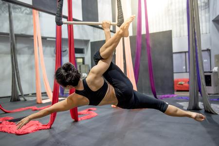 Jonge Aziatische gymnast vrouw doet gymnastiek op touw in lucht fitness gym