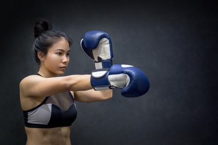 sexy asian woman: Beautiful young Asian woman posing with blue boxing gloves, black background Stock Photo