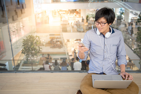 Young Asian man dressed in casual style using smartphone and laptop. Digital nomad working in co working space, modern IT lifestyle with work life balance concept.