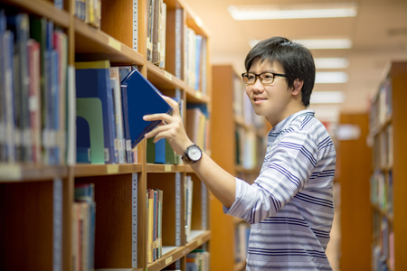 učebnice: Young Asian man university student choosing book in library, education research and self learning in university life concepts