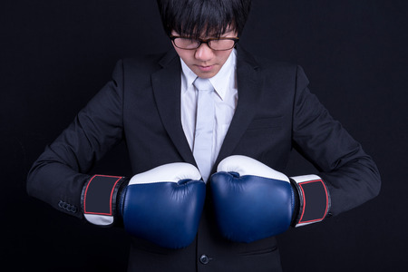 young asian business man wearing suit and posing  with blue boxing gloves in black background studio. business man fight pose concept Stock Photo