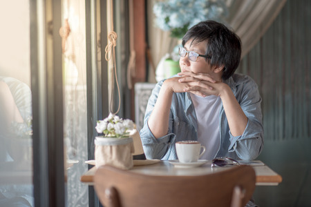 Young Asian happy man relaxing during coffee time in cafe, casual lifestyle on vacation concepts