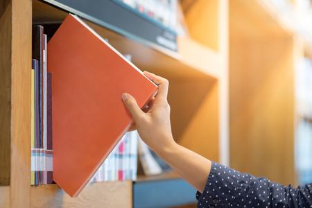 männliche Hand, die orange Buch in der öffentlichen Bibliothek, in der Bildungsforschung und im Selbstlernen in den Hochschullebenkonzepten wählt und auswählt Standard-Bild