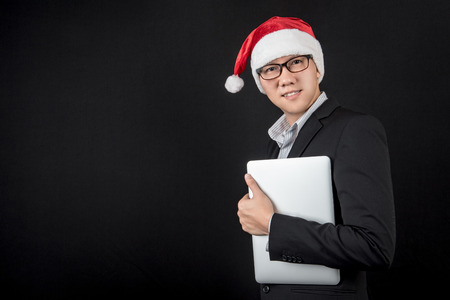 Young Asian businessman wearing suit and santa hat holding laptop computer on black background, male entrepreneur in christmas holiday and new year party concepts