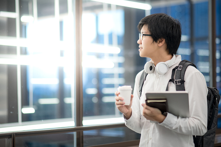 Young Asian man university student holding laptop computer, notebook and coffee cup, happy lifestyle in college, educational concepts
