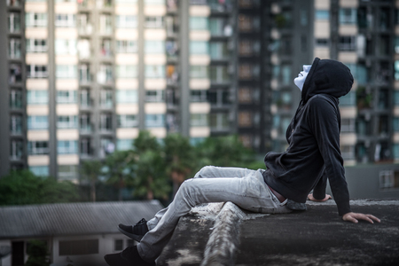 Mystery man in white mask wearing hoody sitting on rooftop of abandoned building and look up in the sky feeling lonely, self destruction suicidal addiction or major depressive disorder concepts