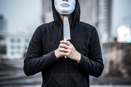 Mystery man in white mask putting knife on his throat considering suicide. depression self destruction suicidal addiction drug. major depressive disorder concept