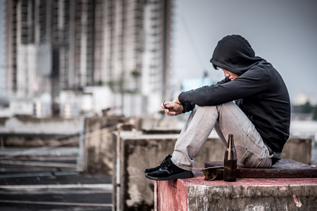 Mystery man in hoody jacket, sitting and hugs his knees up with an empty and broken bottle. depression self destruction suicidal addicts drug, Major depressive disorder concept Standard-Bild