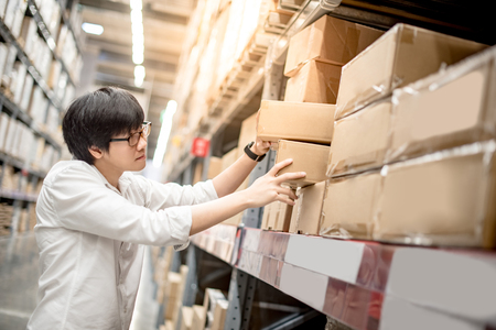 Young Asian man picking paper box from shelf in warehouse, shopping warehousing or packing products concepts