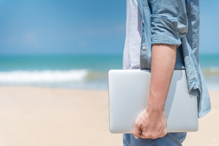 Male hand holding laptop on the beach, working outdoor in summer season, digital nomad man lifestyle concepts