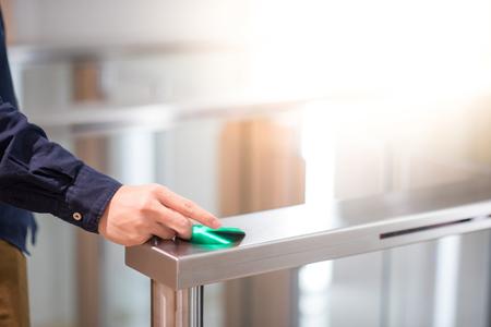 Mano masculina con tarjeta inteligente para abrir la máquina de puerta automática en edificio de oficinas