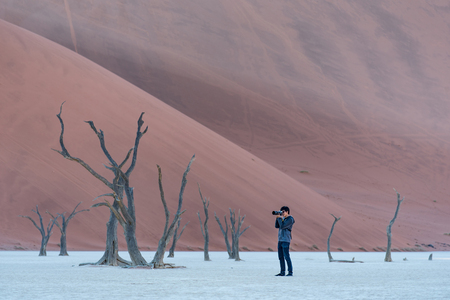 Young male photographer and traveler taking photo of dead tree in deadvlei (Sossusvlei), famous natural landmark in Namib desert of Namibia, Africa. Travel photography concept Stock Photo