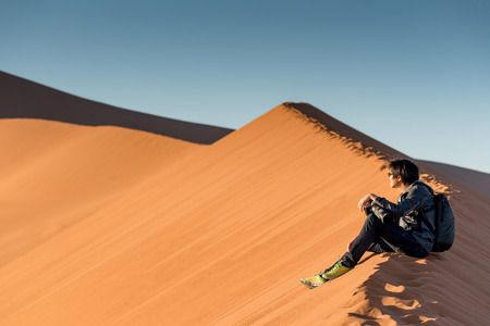 Young male traveler and photographer sitting on the top of sand dune looking at sunrise or sunset in desert of Namibia, Africa. Travel photography concept Stock Photo