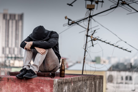 Mystery man in hoody jacket, sitting and hugs his knees up with an empty and broken bottle. depression self destruction suicidal addicts drug, Major depressive disorder concept Stock Photo