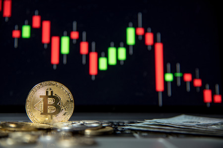 Studio shot of bitcoin gold silver coins and dollar bank note on laptop keyboard with basic candlestick green red graph price in background. Worldwide cryptocurrency and digital payment concepts Banque d'images