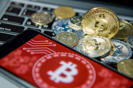 Bitcoin gold silver coins and smartphone with red graphic background screen on laptop keyboard. Close up and focus on Bitcoin. Worldwide cryptocurrency and digital payment concepts Stock Photo