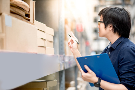 Young Asian man doing stocktaking of product in cardboard box on shelves in warehouse by using clipboard and pen. physical inventory count concept Stockfoto