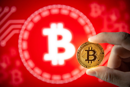 Male hand showing bitcoin gold coin on red graphic background. Close up and focus on bitcoin. Worldwide cryptocurrency and digital payment concepts