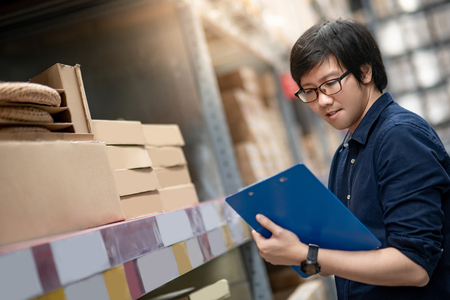 Young Asian man doing stocktaking of product in cardboard box on shelves in warehouse by using clipboard and pen. physical inventory count concept Stock Photo